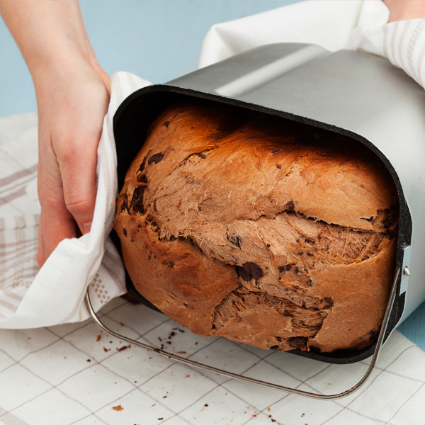 home made bread being taken out of a breadmaker