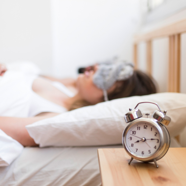 sleeping couple in bed with alarm clock on side table